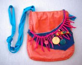 Hot tropical purse; leather little bag with a tiny wild parrot.  Leather is red and blue.