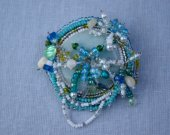 Brooch with aqua donut and a multitude of glass beads:  barrels, rounds, seeds, facets, in aqua, white, dark blue