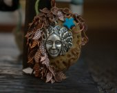 Oregon beach stone: a lady's face surrounded by a forest of tiny leaves, hammered wirework and a turquoise star