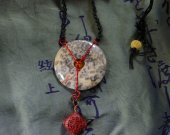 Donut stone of gray, cream, red accents. Necklace of delicate bird bone, carved Chinese bead, shell fish. Adjustable.