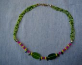 Green glass lozenges are set against hot pink beads, transparent and welcoming the light. Reversible