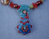 Hot summer colors sizzle with the cool evening blue of the seed beaded bail and focal bead.
