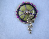 "Donut stone brooch of green with purple wirework and small dragon reaching for ""gem"" at center of stone"