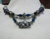 Memory wire choker with dangling bead in blue, black and silver