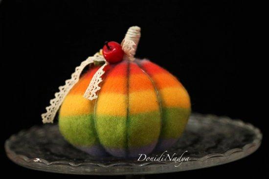 Rainbow pumkin Halloween decoration. Multicolour pumpkin with miniature sunflower, apples and ladybug